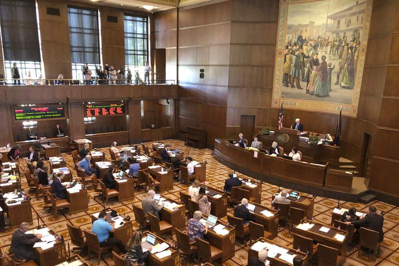 FILE - In this June 20, 2019, file photo, lawmakers convene at the Oregon Senate in Salem Ore. Walkouts by Republicans in Oregon's Legislature have become so frequent, with GOP lawmakers torpedoing progressive legislation, that Democrats want to sanction boycotters with $500 daily fines and even disqualify them from holding office. Democrats hold the majority in the state House and Senate. ( AP Photo/Andrew Selsky, File)