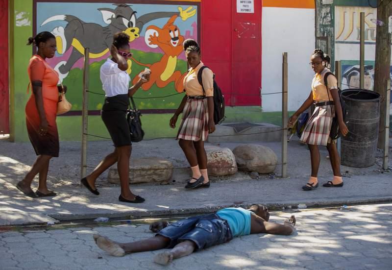 Varias mujeres caminan junto al cadver de un recluso en una calle cerca de la prisin civil de Croix-des-Bouquets, despus de un intento de fuga, el jueves 25 de febrero de 2021, en Puerto Prncipe, Hait. (AP Foto/Dieu Nalio Chery).