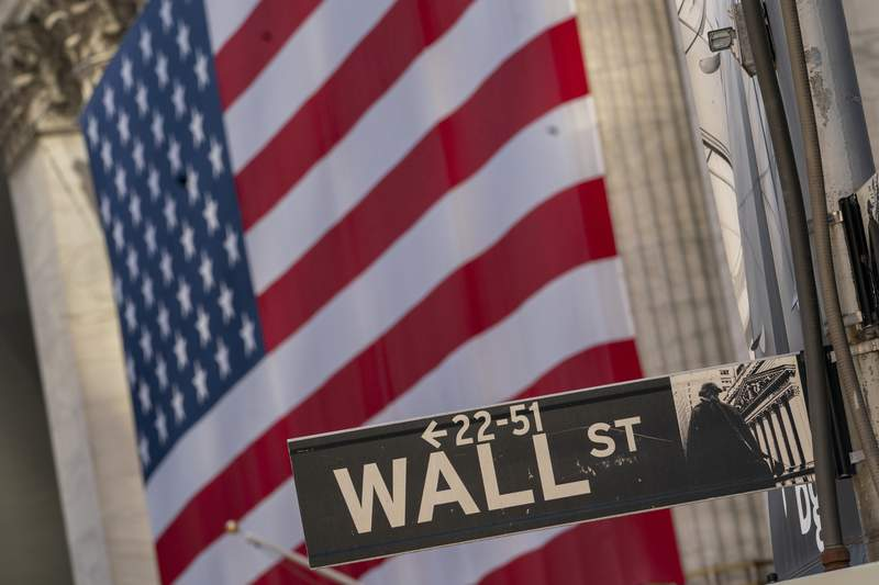 FILE - In this Monday, Sept. 21, 2020, file photo, the Wall Street sign is framed by a giant American flag hanging on the New York Stock Exchange. Stocks are edging lower on Wall Street in early trading, Tuesday, Oct. 13, 2020, as the market cools off following a four-day rally. (AP Photo/Mary Altaffer, File)