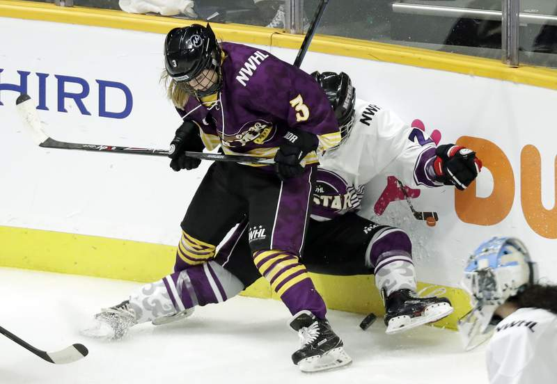 FILE- In this Feb. 10, 2019, file photo, Jonna Curtis, left, a forward on Team Stecklein, battles for the puck with Michelle Picard, right, a defender on Team Szabados, during the NWHL All-Star Hockey Game in Nashville, Tenn. The women's hockey league thinks it can make it work with the same kind of COVID-19 testing the NBA used in its Disney World bubble. Players, coaches and staff will essentially be limited to hotel and Herb Brooks Arena, the site of the 1980 Miracle on Ice that serves as a historic setting for a unique season.  (AP Photo/Mark Humphrey, File)
