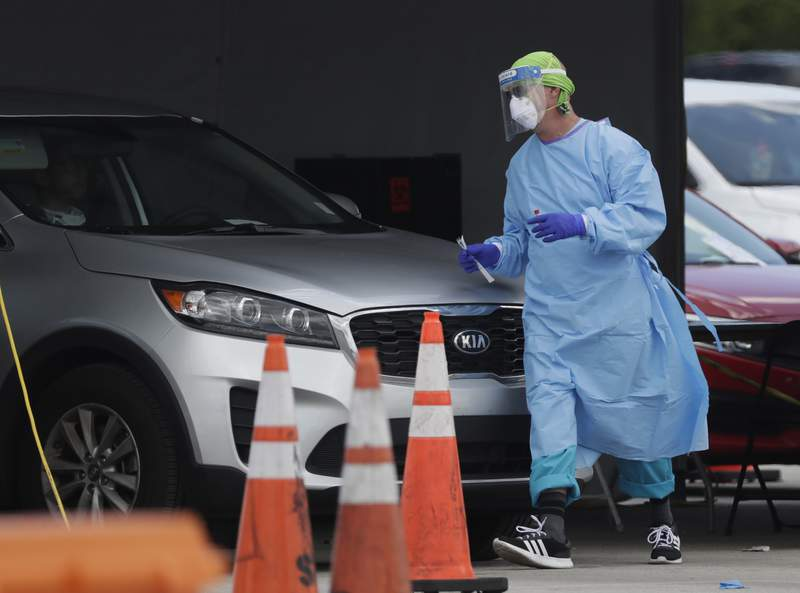 A healthcare worker walks around a car to test a passenger at a drive-through COVID-19 testing site outside Hard Rock Stadium in Miami Gardens.