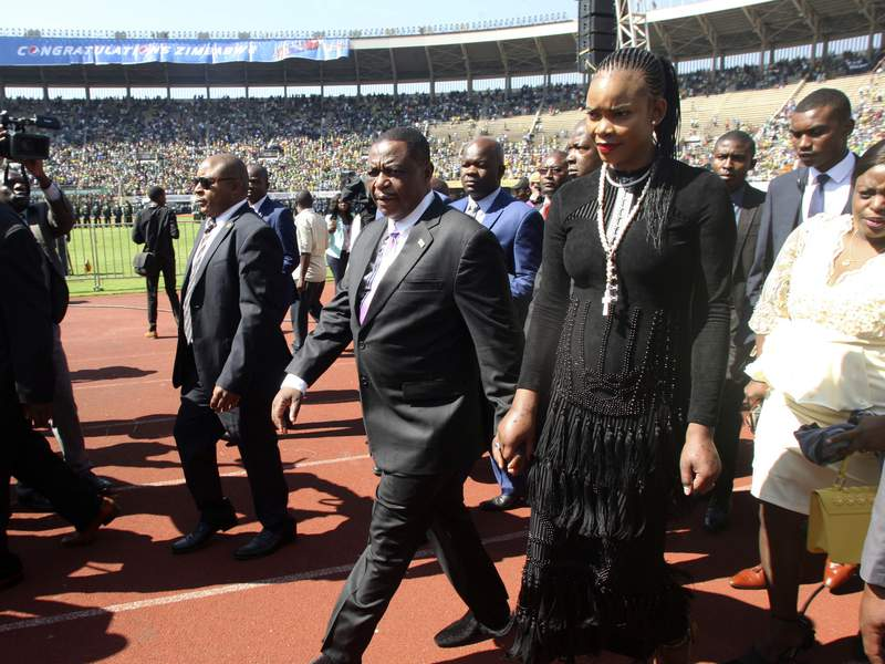 FILE  In this Sunday, Aug. 26, 2018 file photo Zimbabwean Deputy President Constantino Chiwenga is seen with his wife Marry, right, upon arrival for the inauguration ceremony of President Emmerson Mnangagwa, at the National Sports Stadium in Harare.  Marry Chiwenga has been charged with attempting to kill her husband and has also been charged with money laundering and fraud. (AP Photo/Wonder Mashura, File)
