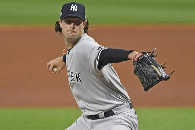 FILE - New York Yankees starting pitcher Gerrit Cole throws in the first inning of Game 1 of an American League wild-card baseball series against the Cleveland Indians in Cleveland, in this Tuesday, Sept. 29, 2020, file photo. The average Major League Baseball salary dropped for an unprecedented third straight year, even before the shortened season caused by the novel coronavirus pandemic. The average fell despite Gerrit Cole, Stephen Strasburg, Anthony Rendon and Christian Yelich all starting long-term contracts guaranteeing $215 million or more. (AP Photo/David Dermer)