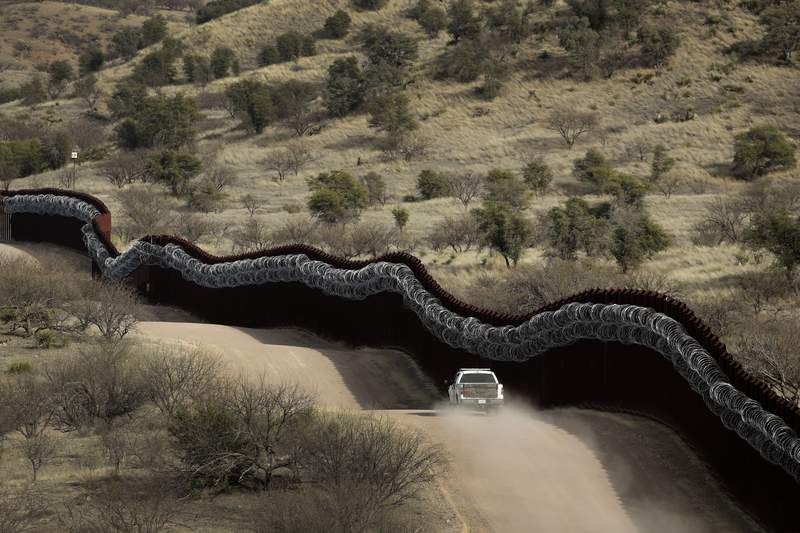 FILE - This March 2, 2019, file photo, shows a Customs and Border Control agent patrolling on the US side of a razor-wire-covered border wall along the Mexico east of Nogales, Ariz. A North Dakota construction company favored by President Donald Trump has received the largest contract to build a wall along the U.S.-Mexico border. The Army Corp of Engineers also said there was no set date to start or complete construction, which will take place near Nogales, Arizona and Sasabe, Arizona. (AP Photo/Charlie Riedel, File)