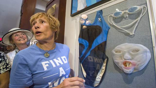 Diana Nyad stands next to the swimming suit, goggles and the custom-made face mask she wore during her historic swim from Cuba to Key West.