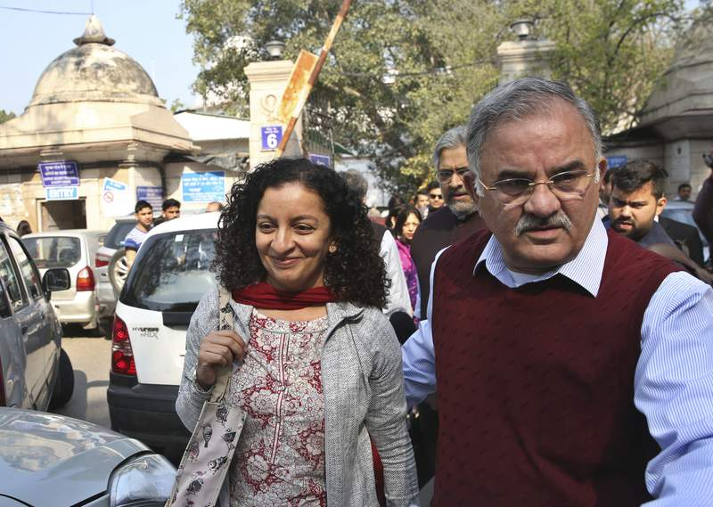 FILE - In this Monday, Feb. 25, 2019, file photo, Indian journalist Priya Ramani, left, smiles as she leaves Patiala House Court in New Delhi, India. A New Delhi court on Wednesday, Feb. 17, 2021, acquitted Ramani of criminal defamation after she accused a former editor-turned-politician and junior external affairs minister of sexual harassment. M.J. Akbar, now 70,  filed a case against Ramani in Oct. 2018, denying the allegations as false, baseless and wild. (AP Photo/File)