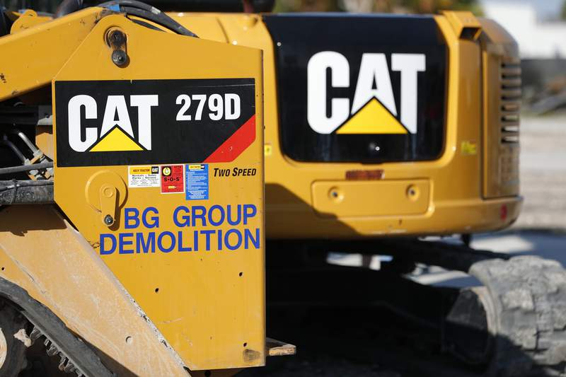 FILE - This May 8, 2019 photo shows a Caterpillar 279D Compact Track Loader, left, and 308E2 CR Mini Hydraulic Excavator, right, rear, at a demolition site in Fort Lauderdale, Fla.  Caterpillar's revenue climbed in the second quarter as the machinery company experienced increased demand for its equipment and dealer inventories improved.  Revenue for the Deerfield, Illinois-based company rose to $12.89 billion from $10 billion, Friday, July 30, 2021.   (AP Photo/Wilfredo Lee, File)