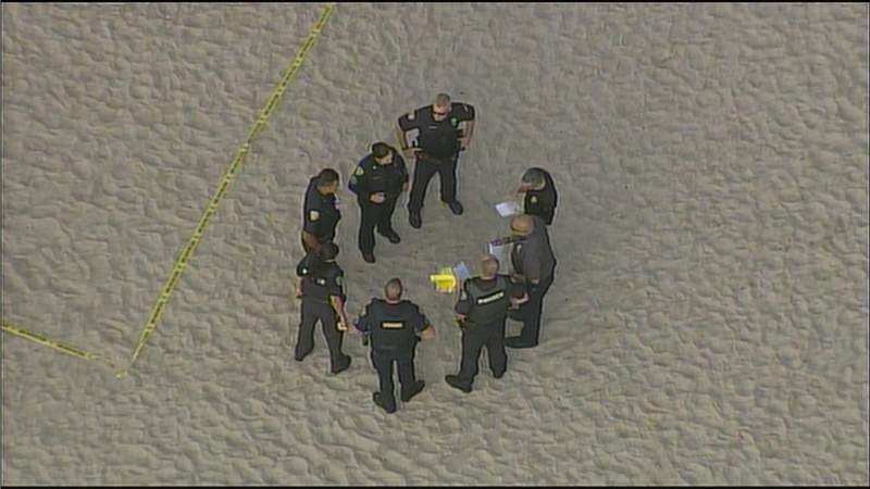 Fort Lauderdale police gather on the beach to investigate the deaths of two people.