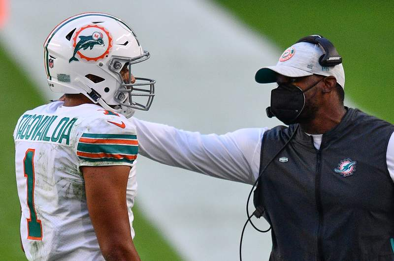 Head Coach Brian Flores of the Miami Dolphins speaks with Tua Tagovailoa #1 during the game against the Los Angeles Chargers at Hard Rock Stadium on November 15, 2020 in Miami Gardens, Florida.