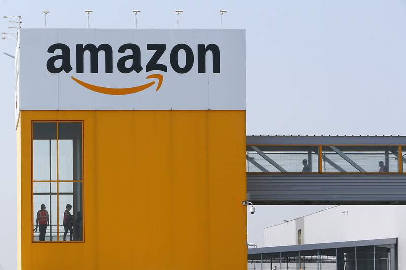 FILE - In this April 9, 2020, file photo, employees observe social distancing due to coronavirus, at the entrance of Amazon, in Douai, northern France. Amazon announced Tuesday, Feb. 2, 2021, that Jeff Bezos would step down as CEO later in the year, leaving a role hes had since founding the company nearly 30 years ago. (AP Photo/Michel Spingler, File)