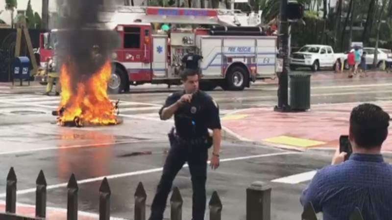 A police officer stands near a scooter that burst into flames after crash on Wednesday in Miami Beach.