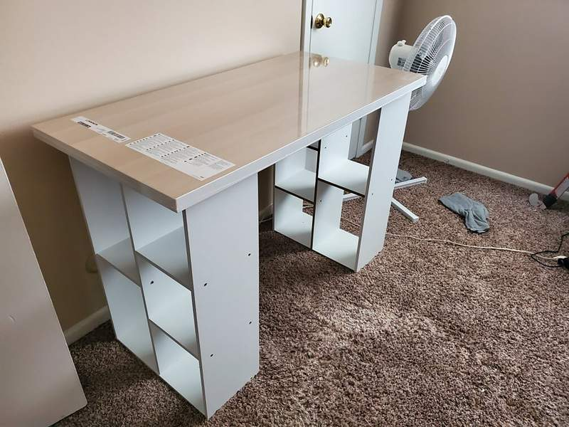 In this photo provided by Megan Fry, a desk Fry constructed out of a legless tabletop and bookcases stands in her Indianapolis home on Sept. 14, 2020. First it was toilet paper. Disinfectant wipes. Beans. Coins. Computers. Now, desks are in short supply because of the coronavirus pandemic. Its not as cute or trendy as a bought desk and I wish it had drawers for storage, said Fry, who is starting a new work-from-home customer service job in Indianapolis in October.  But Im happy its clean and has a large surface on top for my monitors and laptop. (Megan Fry via AP)