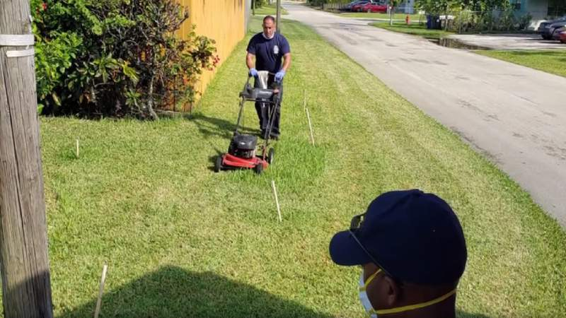 Firefighter cuts grass outside elderly man's home in Fort Lauderdale.