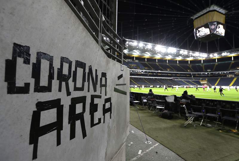 Eintracht fans have taped letters at a wall of the stadium during a Europa League round of 16, 1st leg soccer match between Eintracht Frankfurt and FC Basel in Frankfurt, Germany, Thursday, March 12, 2020. The match was played in an empty stadium because of the coronavirus outbreak. For most people, the new coronavirus causes only mild or moderate symptoms, such as fever and cough. For some, especially older adults and people with existing health problems, it can cause more severe illness, including pneumonia. (AP Photo/Michael Probst)