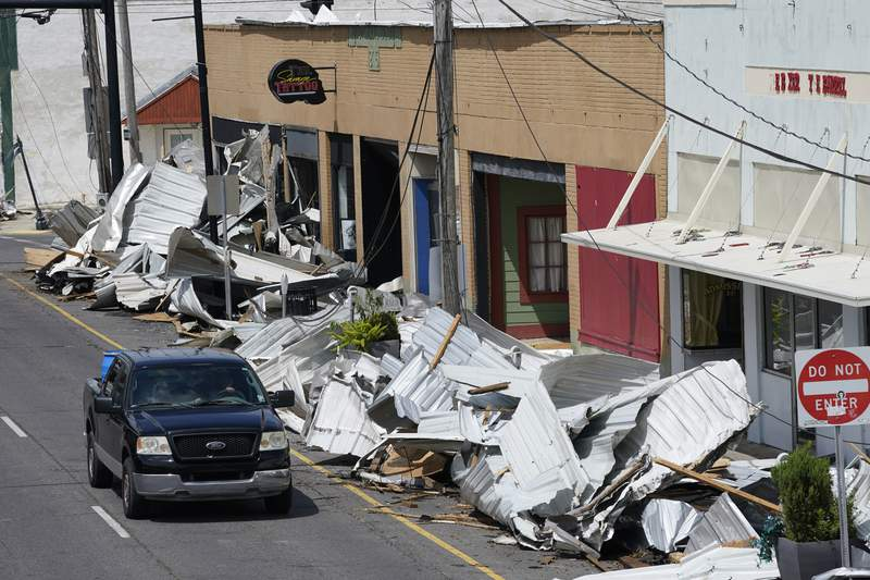 Traffic passes by piles of debris on the sidewalk of Main Street in downtown as residents and try to recover from the effects of Hurricane Ida Tuesday, Aug. 31, 2021, in Houma, La.  Small businesses hit by Hurricane Ida face a slow and daunting recovery as they grapple with storm damage, a lack of power, water and internet service and limited ability to communicate with clients or customers. (AP Photo/Steve Helber)