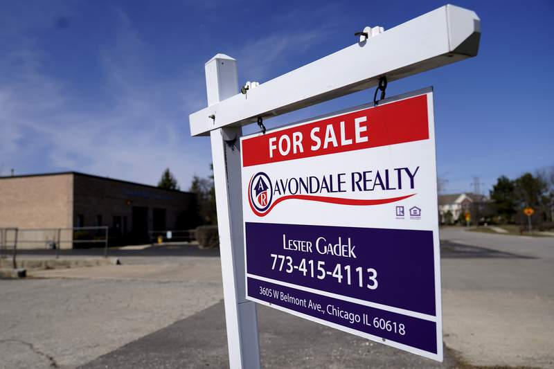 """FILE - In this March 21, 2021 file photo, a """"For Sale"""" sign stands along side a building lot in Wheeling, Ill. Mortgage rates were flat to higher this week, Thursday, June 3. The benchmark 30-year home loan remained below the 3% mark amid continued positive indications of the economys recovery from the pandemic recession.   (AP Photo/Nam Y. Huh, File)"""