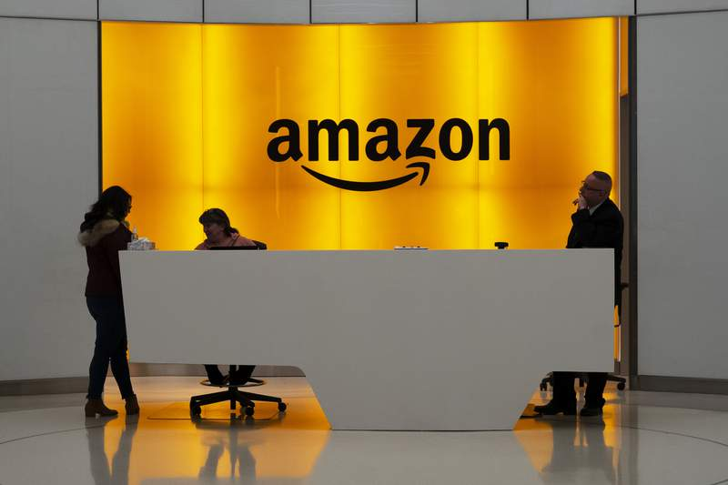 FILE - In this Thursday, Feb. 14, 2019 file photo, People stand in the lobby for Amazon offices in New York. Some Democratic members of Congress and national union leaders have gathered, seeking to build support for unionizing a massive Amazon facility outside Birmingham, Alabama. Mail voting by about 6,000 workers at the distribution facility began in February 2021 and concludes at the end of March.  (AP Photo/Mark Lennihan, File)