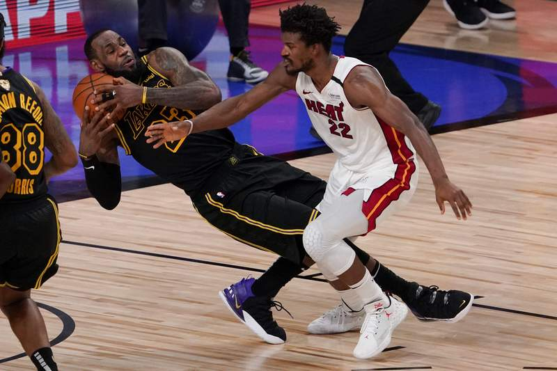 Los Angeles Lakers forward LeBron James pulls rebound away from Miami Heat forward Jimmy Butler during the second half in Game 5 of basketball's NBA Finals Friday, Oct. 9, 2020, in Lake Buena Vista, Fla. (AP Photo/Mark J. Terrill)