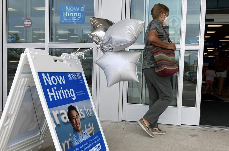 En primer plano, un aviso de empleo afuera de una tienda en Morton Grove, Illinois, el 21 de julio de 2021. (AP Foto/Nam Y. Huh)