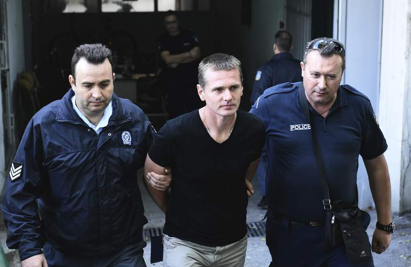 FILE - In this Oct.4, 2017 file photo, police officers escort Alexander Vinnik, center as they leave a courthouse at the northern Greek city of Thessaloniki. The Russian bitcoin fraud suspect Alexander Vinnik goes on trial on Monday in Paris for allegedly having used ransomware in a fraud involving 200 victims and estimated to a global amount of 135 million euros. Alexander Vinnik, who is also wanted in the United States and in Russia, is facing up to ten years in prison in a four-day trial in France over charges of extorsion, money laundering and criminal association. (AP Photo/Giannis Papanikos, File)