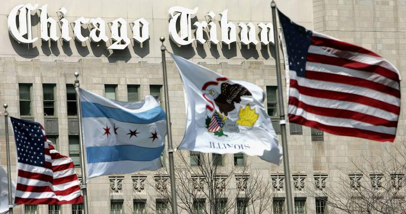 FILE - In this April 12, 2006, file photo, flags wave near the Chicago Tribune Tower in downtown Chicago. Newspaper publisher Tribune has agreed to be sold to Alden Global Capital, a hedge fund known for cutting costs and eliminating newsroom jobs, in a deal valued at $630 billion. Tribune Publishing Co., which owns the Chicago Tribune, the New York Daily News, the Baltimore Sun and other newspapers, said Tuesday, Feb. 16, 2021, it has agreed to sell its shares to Alden for $17.25 apiece, in cash. (AP Photo/Charles Rex Arbogast, File)