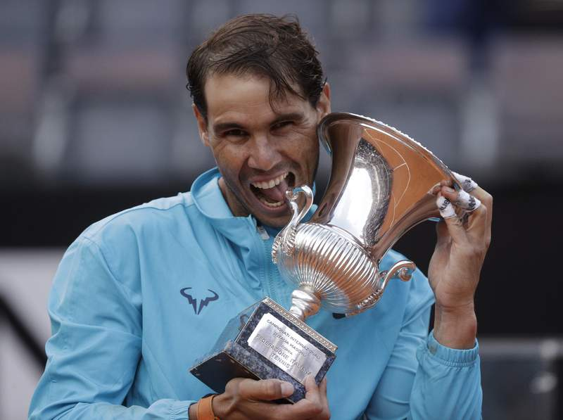 FILE - In this May 19, 2019 file photo, Rafael Nadal of Spain holds his trophy after winning against Novak Djokovic of Serbia at the end of their final match at the Italian Open tennis tournament, in Rome. Rafael Nadal is preparing his return to tennis after a seven-month layoff at next weeks Italian Open. The Foro Italico is always a special place for me and even more so this year as it will be my first tournament following a long period without playing, Nadal, who has won the Rome tournament a record nine times, said in a video message played at the events presentation Tuesday, Sept. 8, 2020. (AP Photo/Gregorio Borgia)
