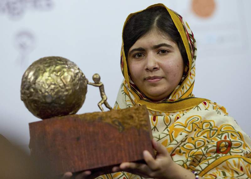 """-FILE- In this Friday Sept. 6, 2013, file image, Pakistani teenager Malala Yousafzai, who was shot and injured by the Taliban for advocating girls' education, poses for photographers after being awarded the International Children's Peace Prize 2013 during a ceremony in the Hall of Knights in The Hague, Netherlands. Sadat Rahman, a 17-year-old Bangladeshi boy has won the International Children's Peace Prize for his work combating cyberbullying in his country. Rahman said Friday, Nov. 13, 2020, at a ceremony in The Hague that the fight against cyberbullying """"is like a war, and in this war I am a warrior,"""" Rahman developed a mobile phone app that provides education and a way to report online abuse after he heard about a 15-year-old girl who killed herself as a result of cyberbullying. (AP Photo/Peter Dejong)"""