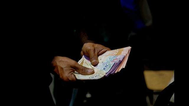 CARACAS, VENEZUELA - APRIL 10: An informal vendor in an unauthorized street market at Petare shows Venezuelan Bolivar bank notes (Sovereign Bolivar) on April 10, 2019 in Caracas, Venezuela   (Photo by Eva Marie Uzcategui/Getty Images)