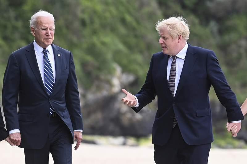 El presidente estadounidense Joe Biden camina junto al primer ministro britnico Boris Johnson afuera del Hotel Carbis Bay, en Cornwall, Bretaa, previo a la cumbre del G7, el 10 de junio de 2021. (Toby Melville/Pool Photo via AP)
