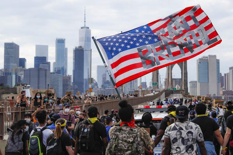 """FILE - In this June 4, 2020, file photo protesters march on the Brooklyn Bridge after a rally in Cadman Plaza Park in New York, following the death of George Floyd, who died after being restrained by Minneapolis police officers on May 25. A coalition of 150 organizations nationwide is opposing the George Floyd Justice in Policing Act. The Movement for Black Lives argues the bill is entrenched in strategies that have historically failed to address police violence across the country and fails to meet the moment."""" The group's opposition comes in a letter to congressional leaders first shared with The Associated Press.  (AP Photo/John Minchillo, File)"""