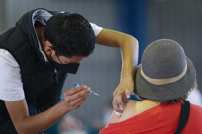 Un trabajador mdico le inyecta a una mujer una dosis de la vacuna rusa Sputnik V contra el COVID-19 el mircoles 24 de febrero de 2021, en el Palacio de los Deportes, distrito de Iztacalco, en la Ciudad de Mxico. (AP Foto/Rebecca Blackwell)