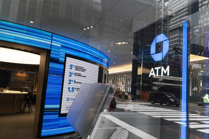 A Chase ATM is open, Wednesday, Jan. 13, 2021 in New York.  JPMorgan Chase & Co., the nations largest bank by assets, said its fourth quarter profits jumped by 42% from a year earlier, as the firms investment bank division had a stellar quarter and the banks balance sheet improved despite the pandemic.  (AP Photo/Mark Lennihan)