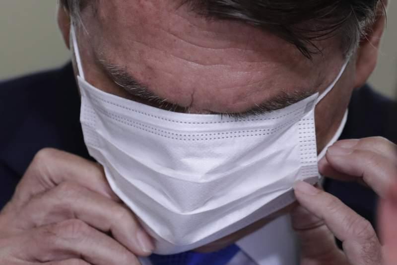 El presidente brasileo Jair Bolsonaro se ajusta su mascarilla durante una conferencia de prensa para anunciar el inicio de la entrega de ayuda de emergencia por la pandemia de COVID-19, el mircoles 31 de marzo de 2021, en el palacio presidencial de Planalto, en Brasilia. (AP Foto/Eraldo Peres)