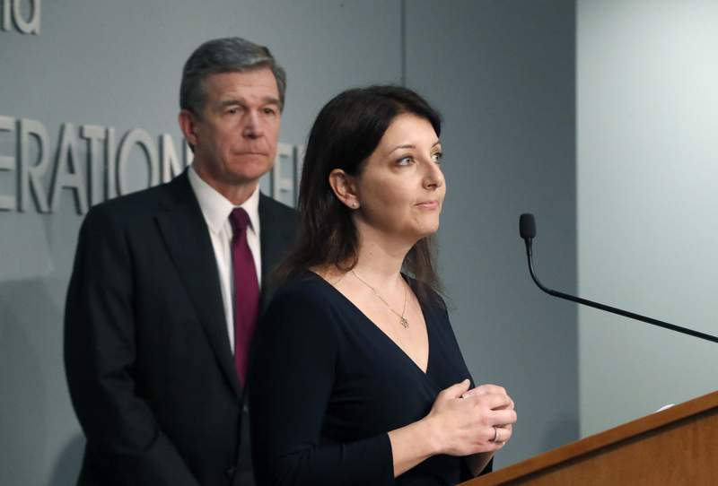 Dr. Mandy Cohen, secretary of the state Department of Health and Human Services, speaks during North Carolina Gov. Roy Cooper's, left, briefing on the coronavirus pandemic at the Emergency Operations Center in Raleigh, N.C., Thursday, May 28, 2020. (Ethan Hyman/The News & Observer via AP)