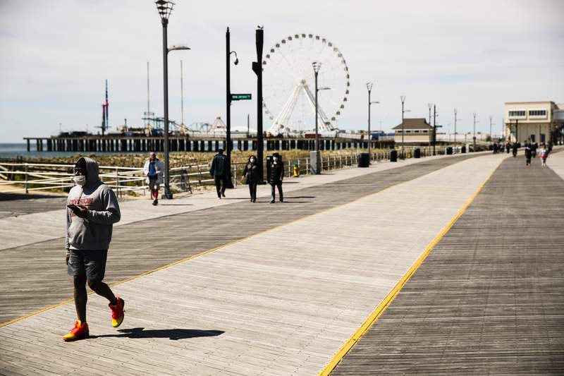 FILE  In this April 28, 2020, file photo, a person, wearing a protective face mask as a precaution against the coronavirus, walks with their phone on the sparsely occupied boardwalk in Atlantic City, N.J. New Jersey launched a website to debunk rumors and hoaxes associated with the spread of the coronavirus, following a false text message of impending national lockdown that circulated widely across the United States. (AP Photo/Matt Rourke, File)