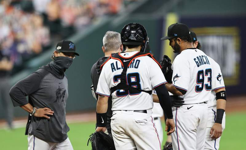 Marlins pitcher Yimi Garcia talks to Manager Don Mattingly during Game 3 of the National League Division Series against the Atlanta Braves at Minute Maid Park in Houston.
