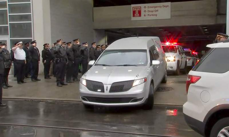In this image provided by WPVI-TV 6ABC, police officers salute as the hearse carrying the body of Philadelphia police officer Cpl. James O'onnor leaves the hospital on Friday, March 13, 2020 in Philadelphia. O'onnor was shot and killed early Friday as he served a homicide warrant at a home in the city's Frankford section.  (WPVI-TV 6ABC via AP)