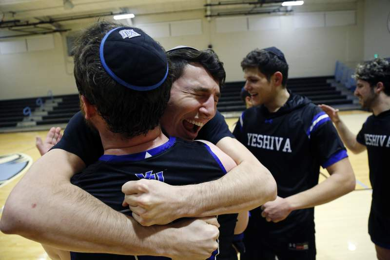 Yeshiva forward Michael Bixon hugs forward Daniel Katz, back to camera, after the team's 102-83 win over Penn State-Harrisburg in the second round of the NCAA men's Division III college basketball tournament Saturday, March 7, 2020, in Baltimore. (AP Photo/Jessie Wardarski)